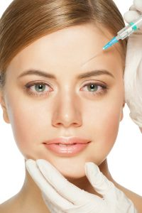 Cosmetic injection of botox to the pretty female face. Isolated on white background